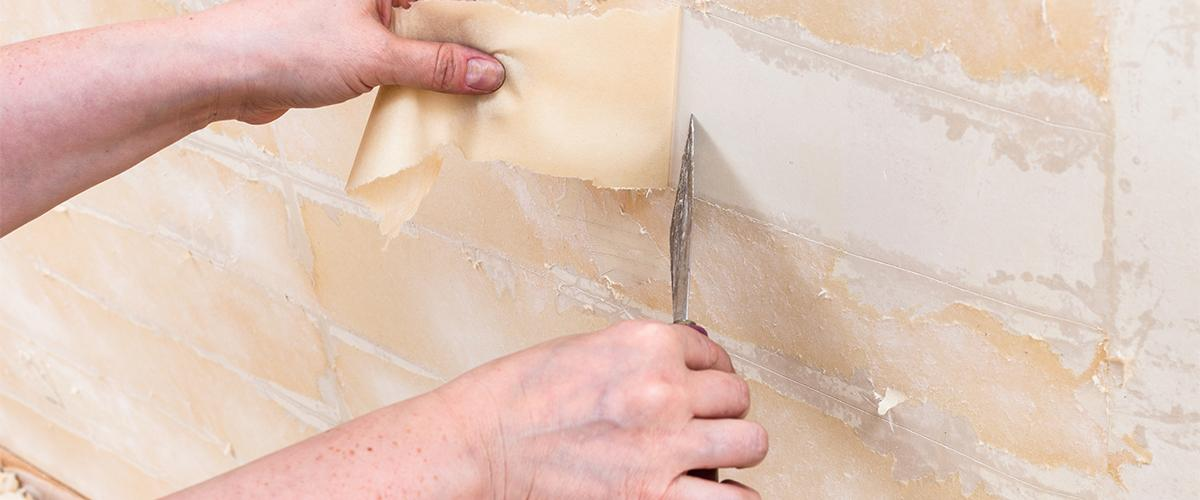 Person removing glue that has been left behind after wallpaper removal